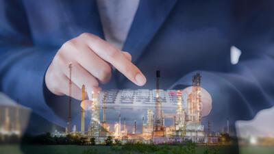 Imagem mostrando contador com calculadora e refinaria de óleo ao fundo